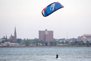 Nick Pucello, 27, of South Portland, kite boards in Back Cove with the city of Portland skyline behind him. Pucello said he surfs quite often, but when the waves aren't good and the wind is high like it was Wednesday, he turns to kite boarding. The kite catches air which pushes him across the water.