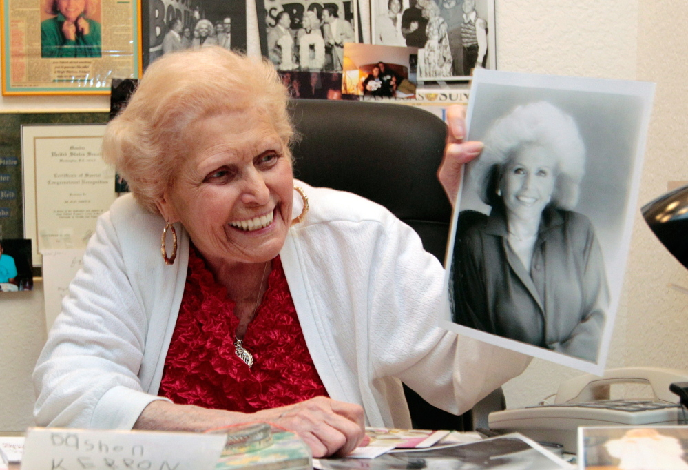 Weight Watchers co-founder Jean Nidetch holds a photo of her younger self. She believed that emotional support and certain eating principles helped people drop pounds.