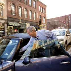 Bruce Campbell of Portland puts a payment slip in his car after parking Thursday on Exchange Street. The chairman of a bicycle and pedestrian committee says funds from added parking revenue would preserve a popular program for safer streets and support the city's general fund.