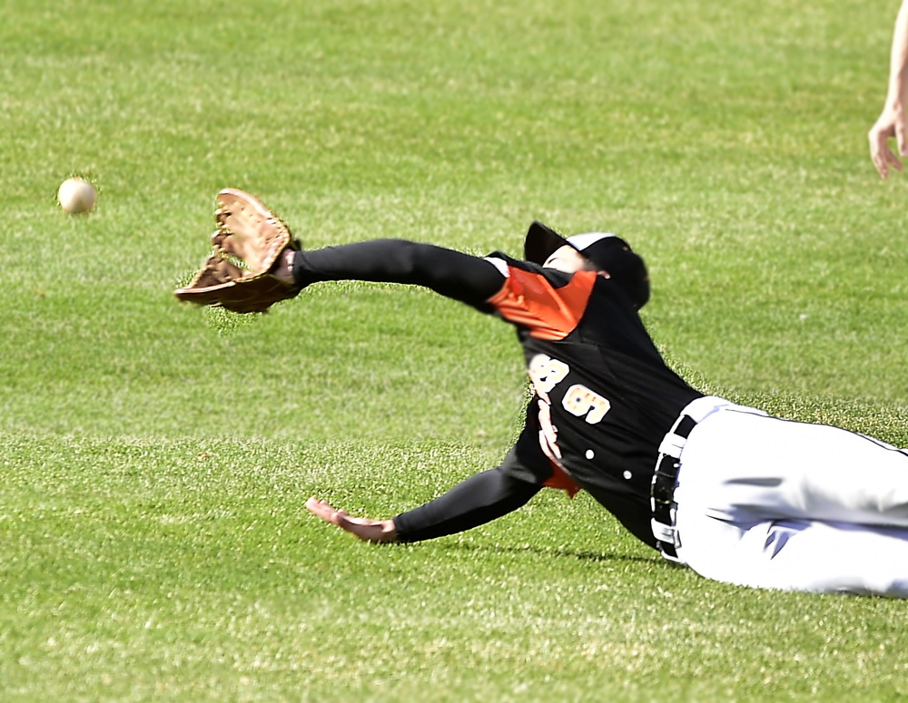 Nick Conley of Biddeford dives in a vain attempt to catch a fly ball hit to center field Thursday during the SMAA game against Deering at Hadlock Field. Deering emerged with a 6-5 victory.