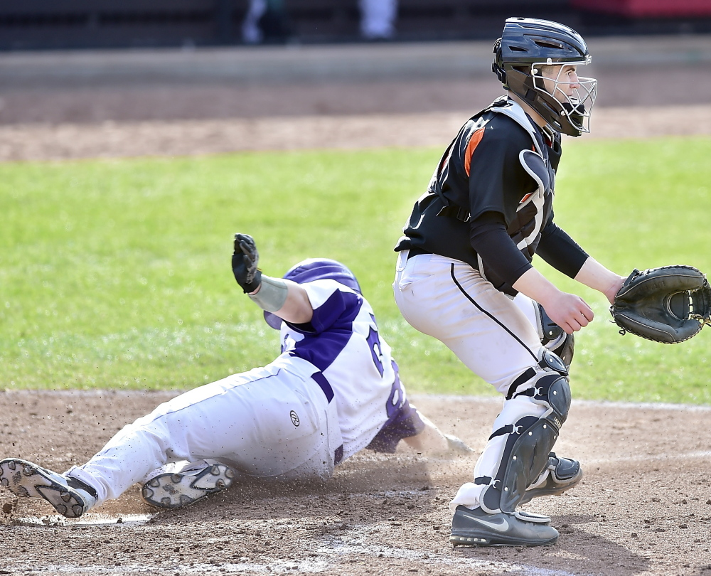 Jake Latini slides home safely to score for Deering as Biddeford catcher Joe Curit waits for a late throw from right field Thursday during Deering's 6-5 victory at Hadlock Field.
