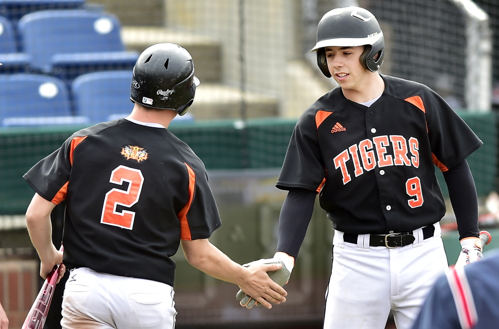 Dominick Day of Biddeford, left, is welcomed by Nick Conley after scoring against Deering in their SMAA game. Deering scored three runs in the seventh inning to walk off with the victory.