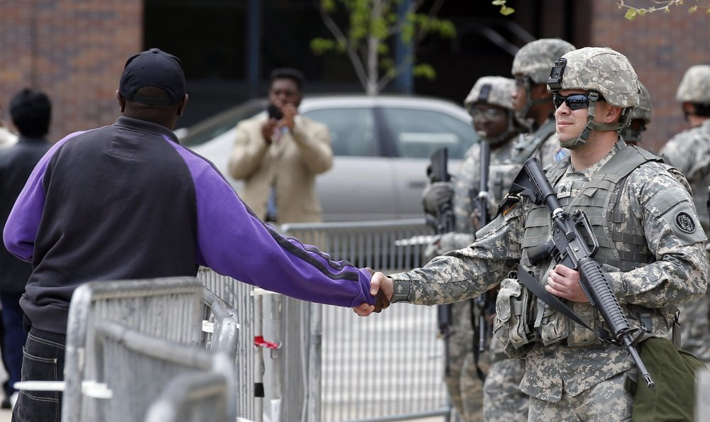 A man shakes hands with a National Guard soldier outside Baltimore City Hall on Friday. State's Attorney Marilyn Mosby announced criminal charges Friday against all six officers suspended after Freddie Gray suffered a fatal spinal injury in police custody. Mosby brought the stiffest charge, second-degree murder, against the driver of the police van involved.