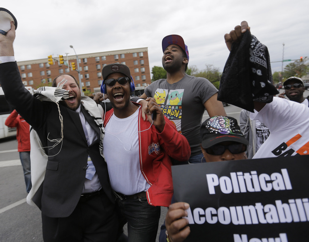 "Rabbi Yerachmiel Shapiro, left, and other citizens celebrate Friday after State's Attorney Marilyn Mosby announced criminal charges against the six officers involved in the Freddie Gray case. She urged protesters to ""channel your energy peacefully."""