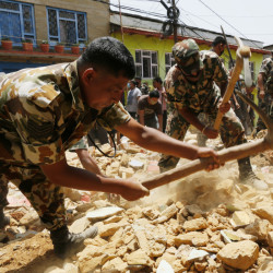 Soldiers dig for a rumored missing person in the rubble of a collapsed house in Manakamana village near the epicenter of Saturday's massive earthquake in Nepal.