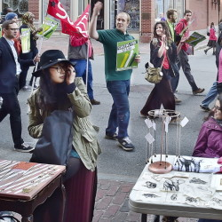 A group that supports raising the minimum wage to $15 an hour marches down Congress Street as artists Alice Shin, left, and Sara Inacio display their wares on Friday. Portland's monthly art walk has a growing focus on political issues.