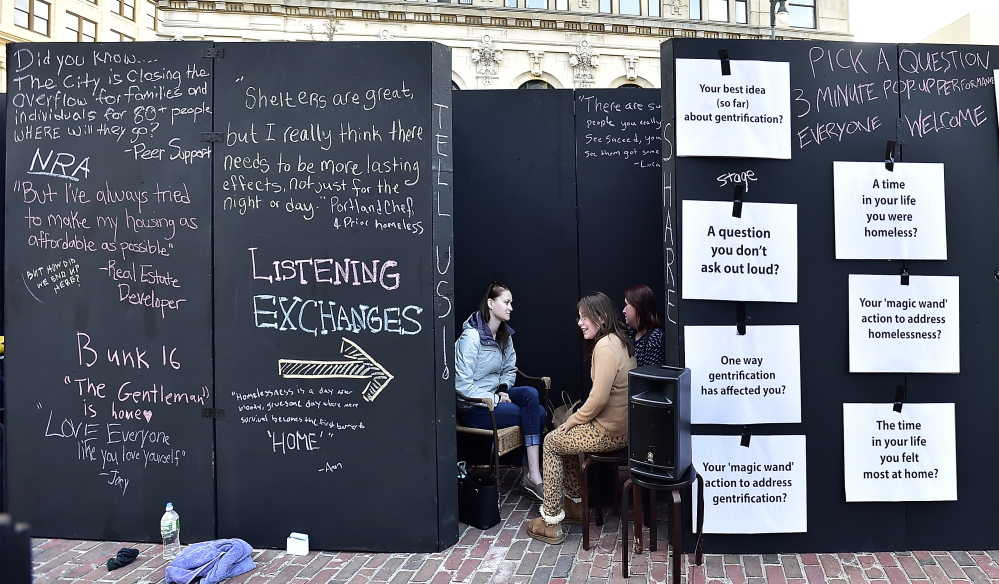 Kelsey Bubar, a social work student at the University of Southern Maine listens to Karen Thuotte, right, and her daughter, Aleah, 10, in a listening wall put up by the professors and students.