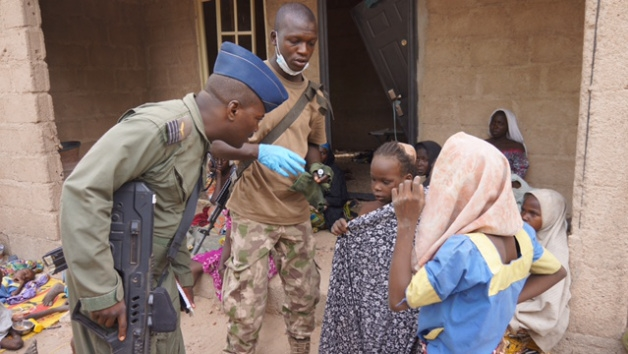 A Nigerian soldier speaks to woman and children that were allegedly rescued by the Nigerian Military after being taken by Islamic extremists in Sambisa Forest, Nigeria.