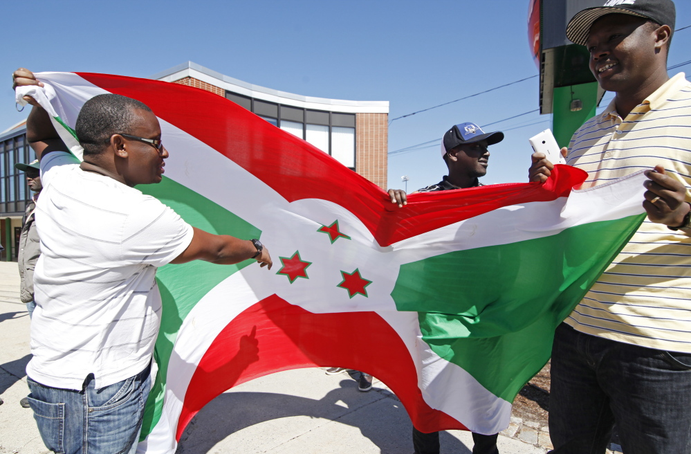 PORTLAND, ME - MAY 2: Yves Florent, Richard Irakoze and Euphrem Manirakiza, all of Lewiston hold the Burundi flag and discuss the three stars reprenting the three Burundi cultural groups  before they and other immigrants from Burundi march from the Portland Expo to Monument Square Saturday, May 2, 2015 to protest the Burundi president who is seeking a third term which goes against the constitution. (Photo by Jill Brady/Staff Photographer)