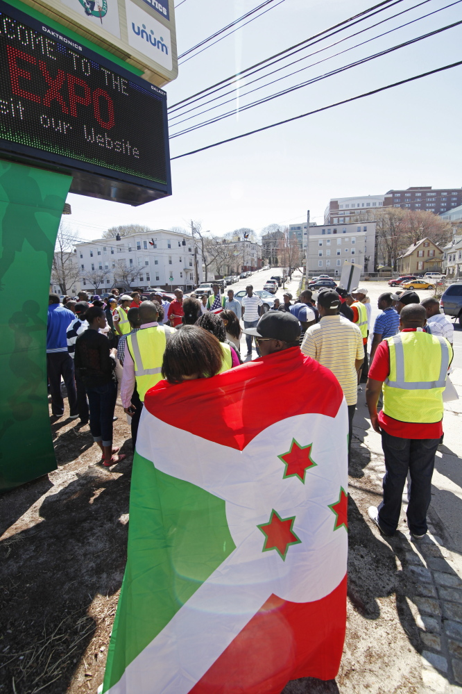 A couple embrace under a Burundi flag as Immigrants from Burundi gather to march from the Portland Expo to Monument Square Saturday. Jill Brady/Staff Photographer