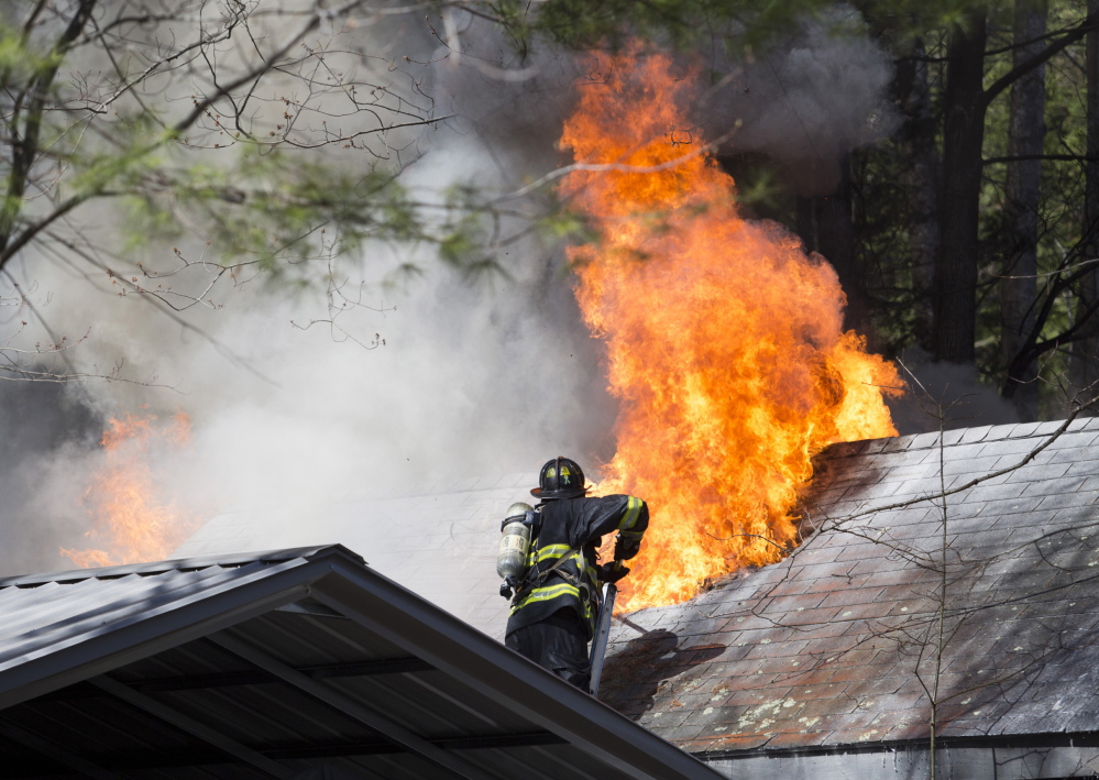 Firefighters fight a blaze at a house on Deering Road in Gorham on Saturday.