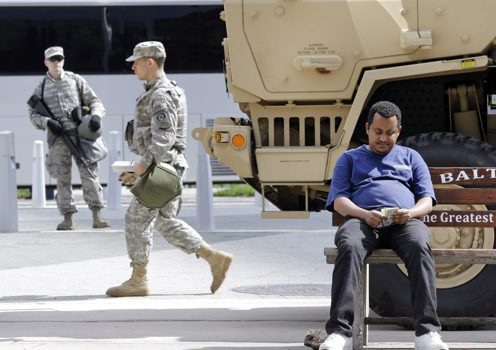 A man sits on a bus stop bench as members of the Maryland National Guard patrol behind him Saturday in Baltimore. The Associated Press