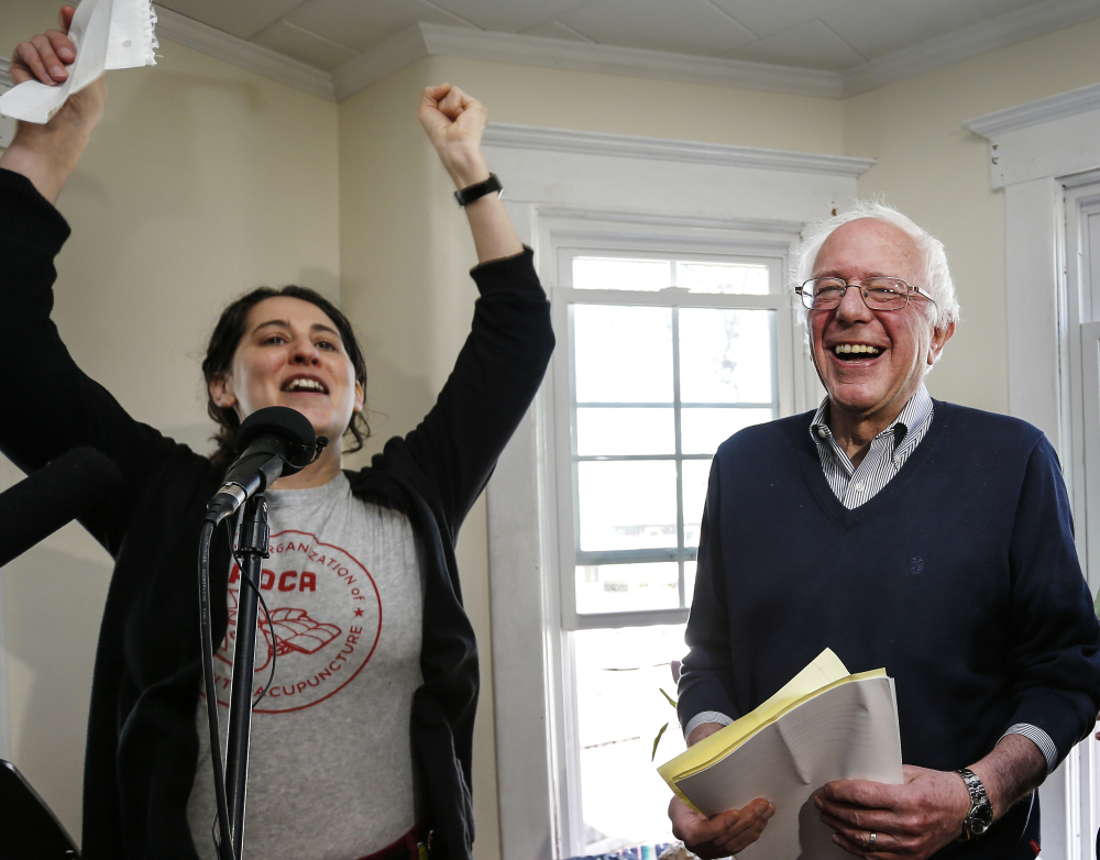 Presidential hopeful Sen. Bernie Sanders, right, greets more than 100 cheering supporters before speaking at a house party in Manchester, N.H., Saturday.