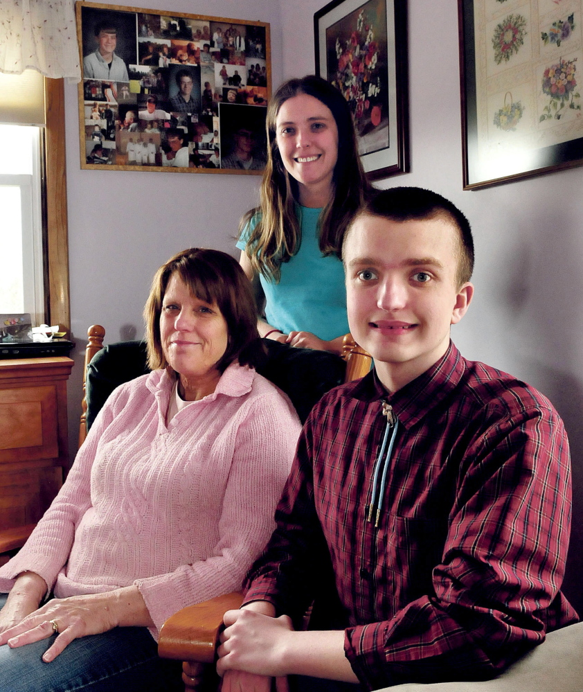 Yvonne Batson with her children Corina and Nathanael at home in Fairfield. Behind them are photographs of Yvonne's son Brendan, who died in 2001. Nathanael, who is legally blind because of a genetic disorder the Batsons share, is close to achieving the rank of Eagle Scout.