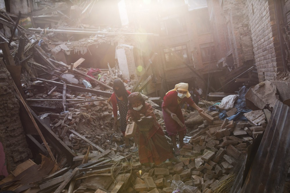 Nepalese woman remove debris searching their belongings from their house that was destroyed a week ago during the earthquake in Bhaktapur, Nepal, Sunday.
