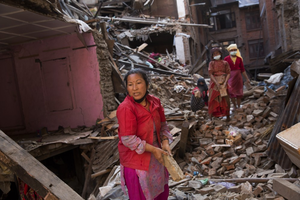 Nepalese women remove debris searching their belongings from their house that was destroyed a week ago during the earthquake in Bhaktapur, Nepal, Sunday.
