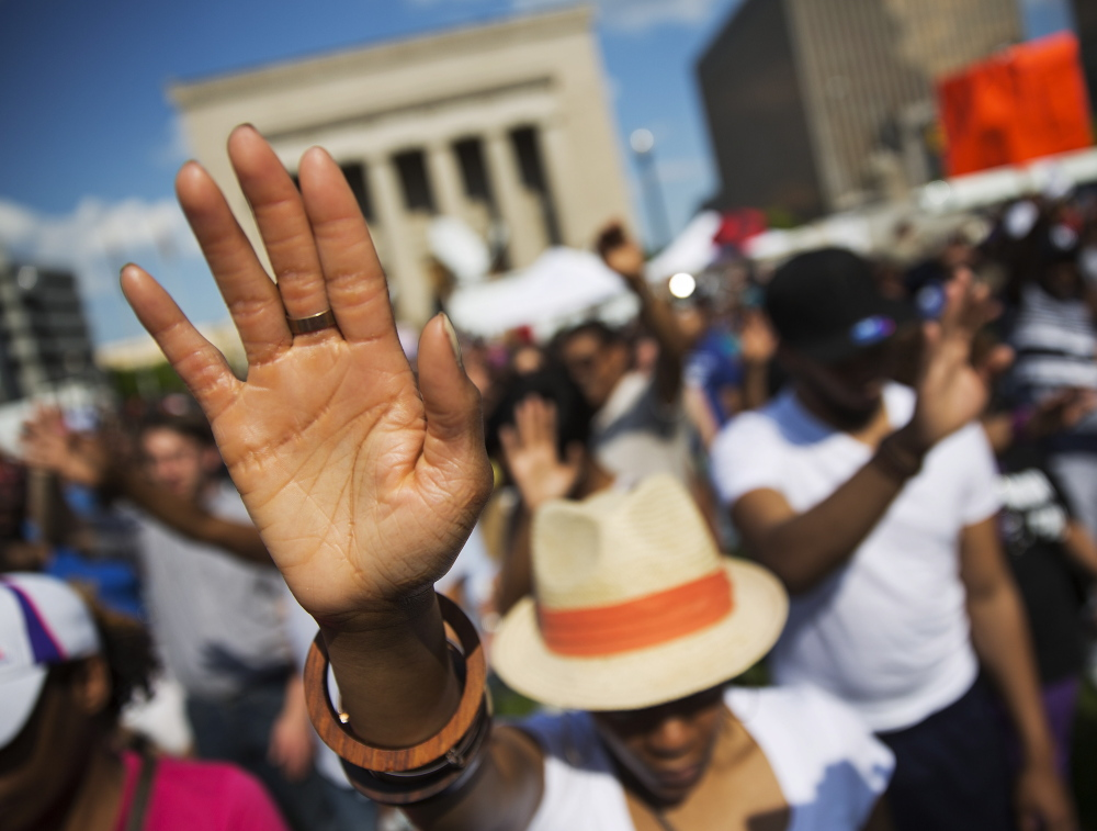 People pray during a rally Sunday at City Hall in Baltimore. A jubilant crowd gathers days after the city's top prosecutor charged six officers involved in Freddie Gray's arrest.