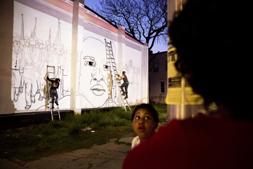 A mural of Freddie Gray is painted on the side of a building by local artist Nether, right, across the street from a makeshift memorial where Gray was arrested in Baltimore. After Gray died from a severe spinal injury while in police custody, civil unrest swept Baltimore.