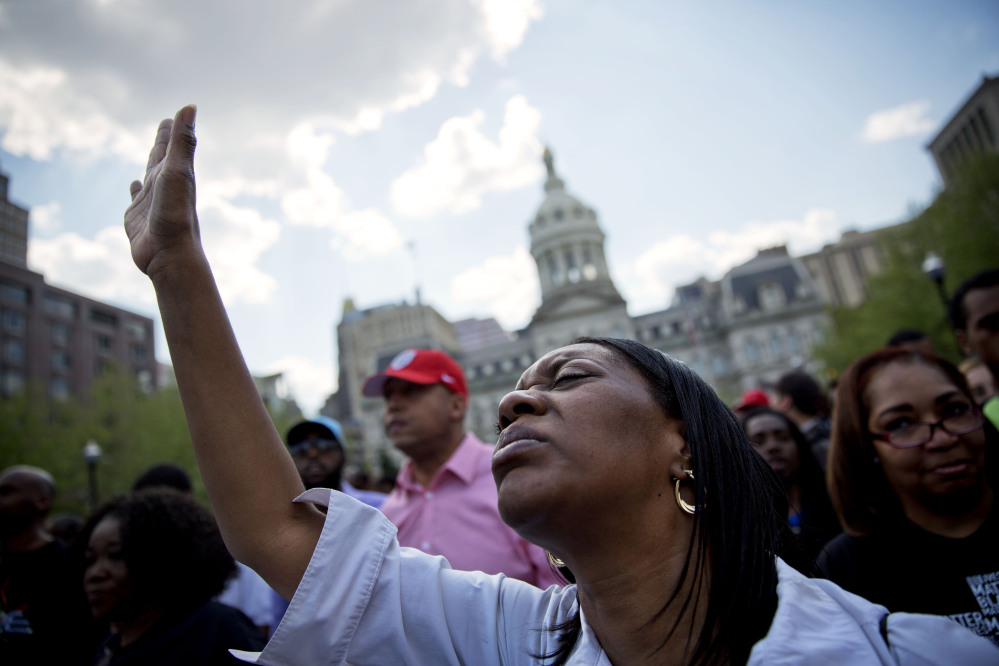 Patricia Freeman prays during a rally in front of City Hall, Sunday in Baltimore.