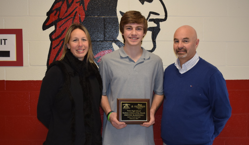 Hunter McDonnell, center, a Wells High School senior, is presented the Student-Athlete of the Month Award by Pamela Moody-Maxon and Activities Director Jack Molloy.