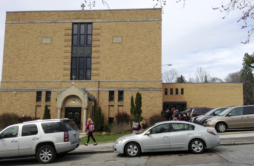 Parents pick up their children at the end of the school day at Christ the King School in Burlington, Vt. The church's sound system that plays recorded bells and hymns has struck a sour note with some neighbors, who find it noisy and intrusive.The Associated Press