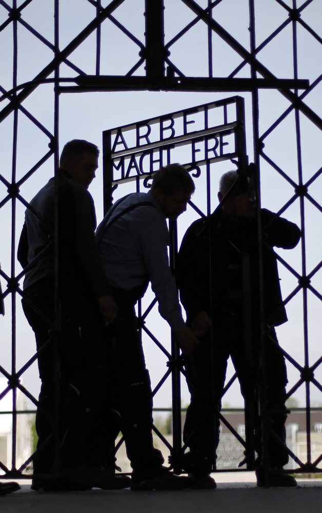 """Blacksmiths prepare a replica of the Dachau concentration camp gate, with the slogan """"Arbeit macht frei"""" (""""Work sets you free"""") at the main entrance to the memorial in Dachau, Germany, on Wednesday. The gate was stolen in November."""
