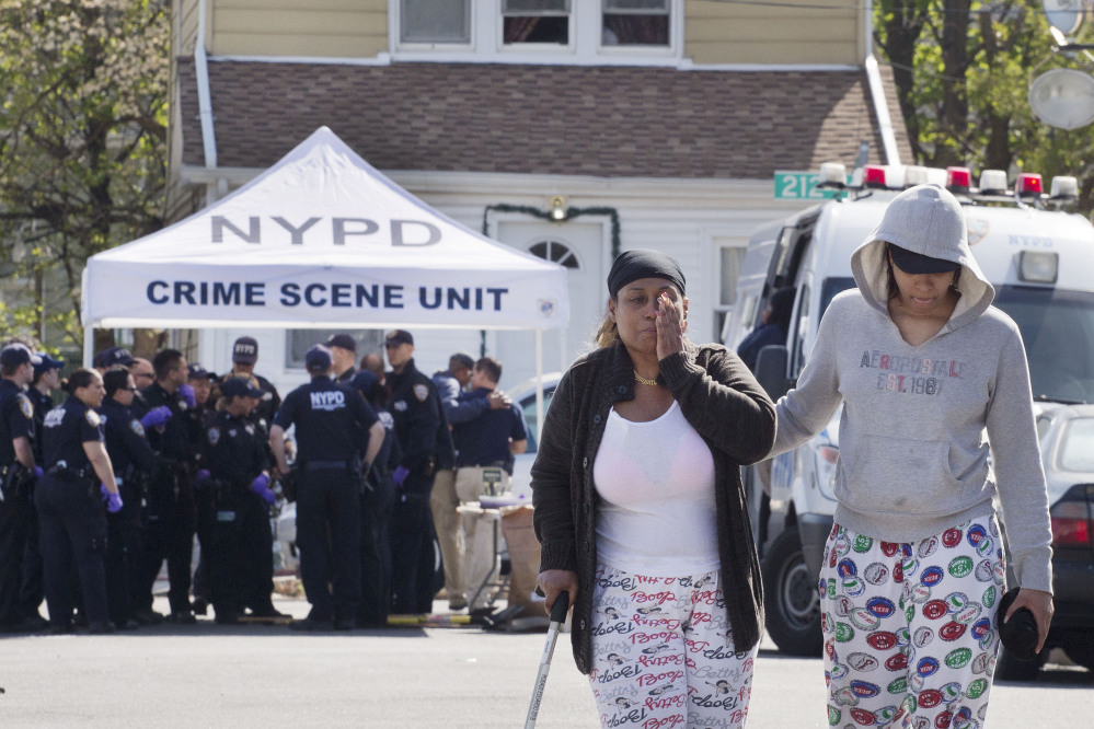 An unidentified woman wipes her face after talking with police officers Sunday about the shooting of a police officer in the Queens borough of New York.