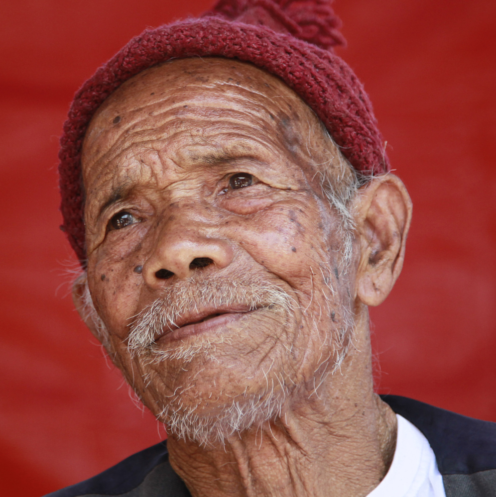 Funchu Tamang, who believes himself to be 101 years old, sits at a makeshift hospital in Bidur, Nuwakot District, Nepal, on Monday. By his own account, he should have died. But when the humble hut of stacked stones collapsed onto Funchu Tamang, his daughter-in-law quickly pulled him from the wreckage.