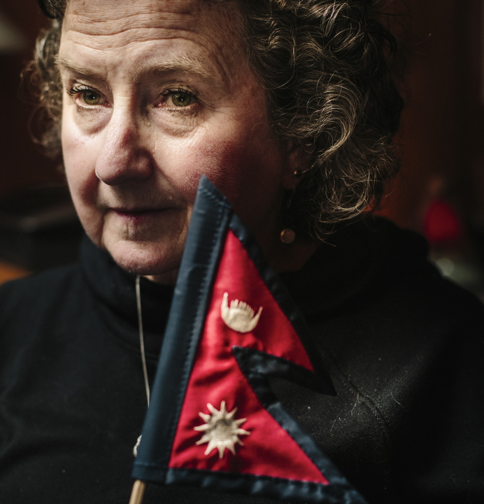 "Kathleen Nolan holds a Nepalese flag Monday at her home. Nolan and her guide were hiking in a national park in Nepal, through a narrow river valley with tall mountains on either side, when a quake struck April 25. ""There was never a moment when we truly felt safe,"" she said."