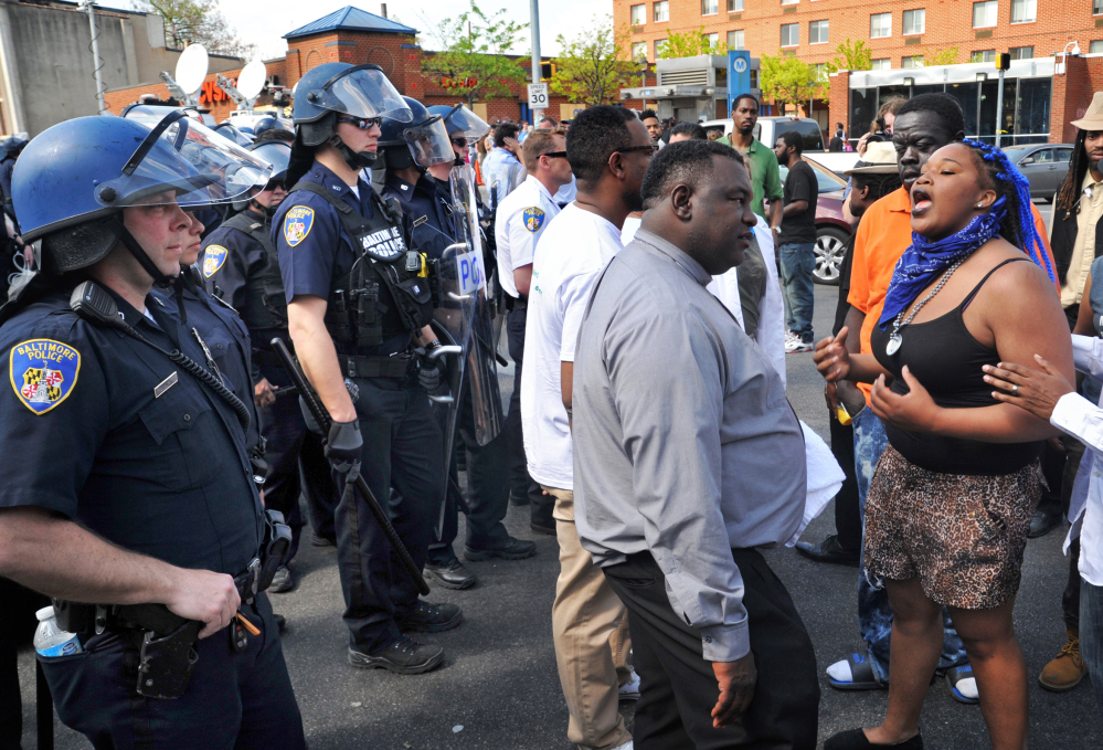 Protesters chant in front of police Monday in Baltimore. Police said they pursued a man who was spotted on surveillance cameras and appeared to be armed with a handgun. The man was taken into custody after a brief chase, during which a gunshot was heard.