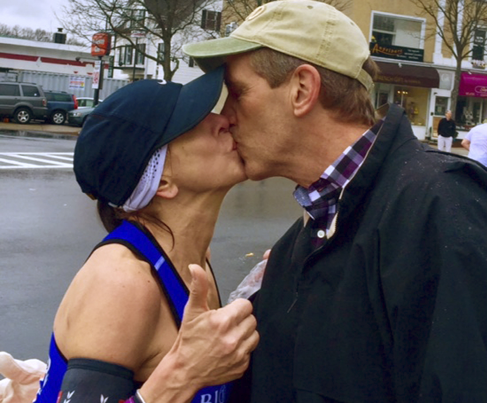 Boston Marathon runner Barbara Tatge, left, kisses an unknown spectator in Wellesley, Mass. After a search, Tatge received a good-humored response from the man's wife.