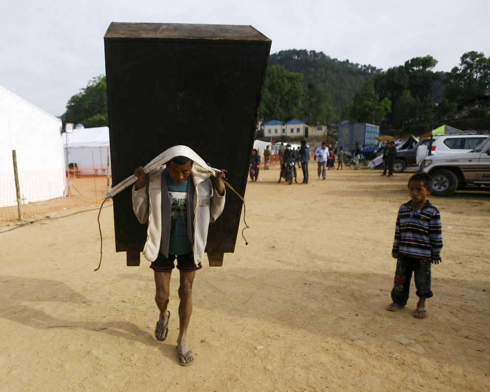 MAY 5: A man carries a cupboard after salvaging it from a collapsed house in Nepal on Tuesday. A woman from Maine is still missing more than a week after the earthquake.
