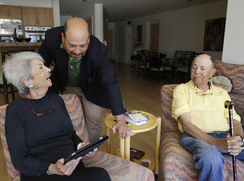 Phil Dworsky visits with his parents, Dorothy and Bill Dworsky, at their home in San Francisco. Each time Dorothy or Bill moves specific items in the house, tiny sensors make notes on a digital logbook, which Phil monitors.
