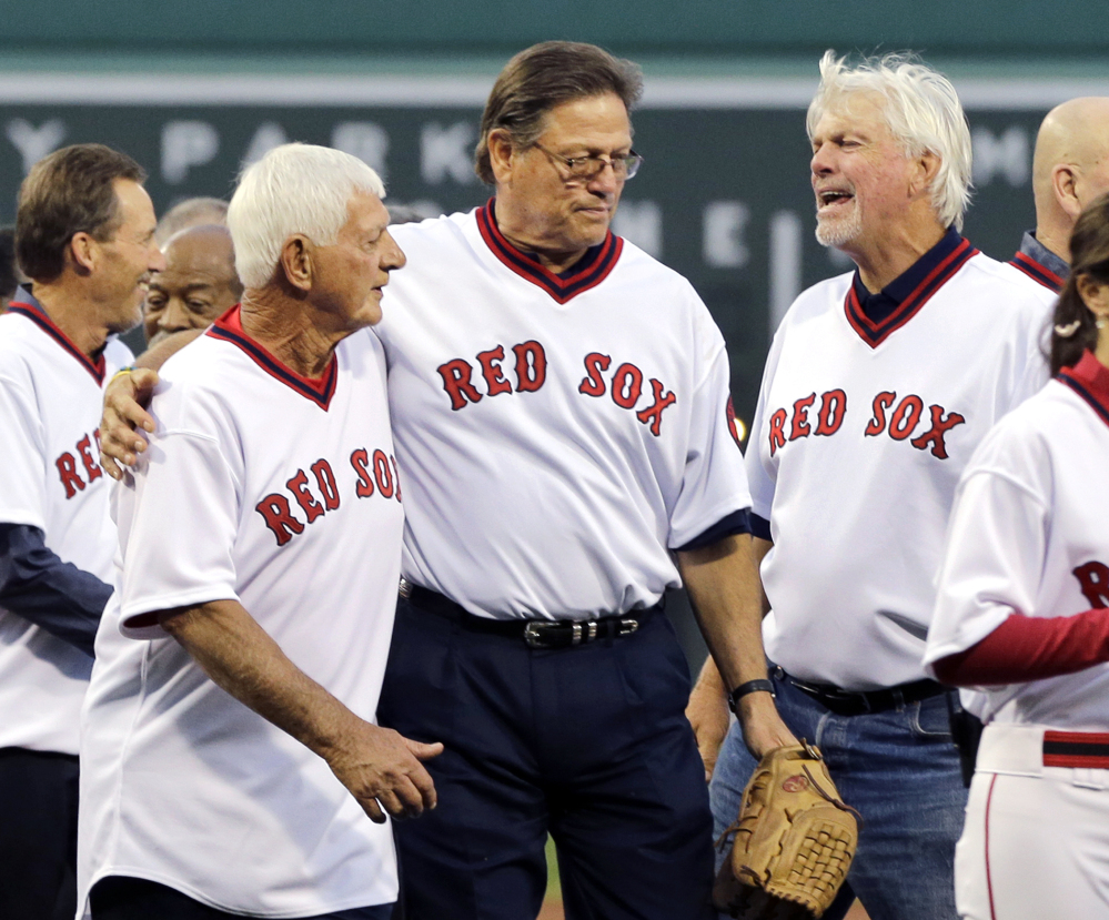 Former Red Sox catcher Carlton Fisk, center, puts his arm around Carl Yastrzemski while Bill Lee, right, chats with them during pre-game ceremonies Tuesday night at Fenway Park honoring the 1975 Red Sox team, which won the American League pennant.