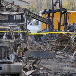 Charred vehicles sit amid the debris of the building that burned Wednesday in Monmouth. One employee of AD Electric was hurt in the fire, and OSHA officials are investigating to determine whether the injured employee or the company violated federal safety standards.