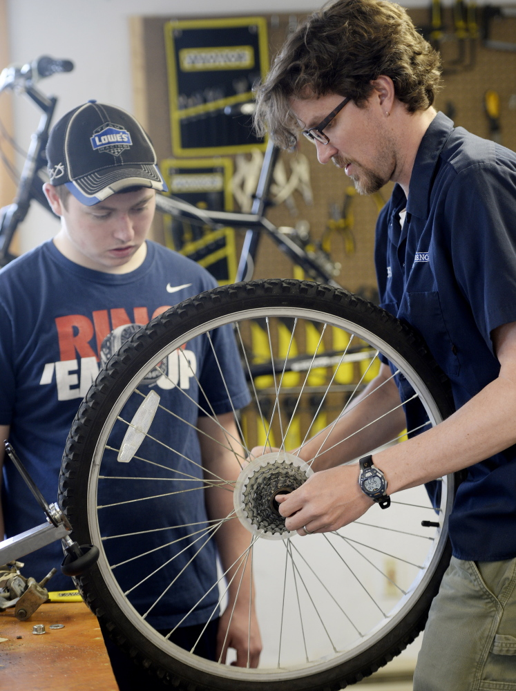 Sophomore Joseph Gately and teacher Shannon Belt work together on a tire.