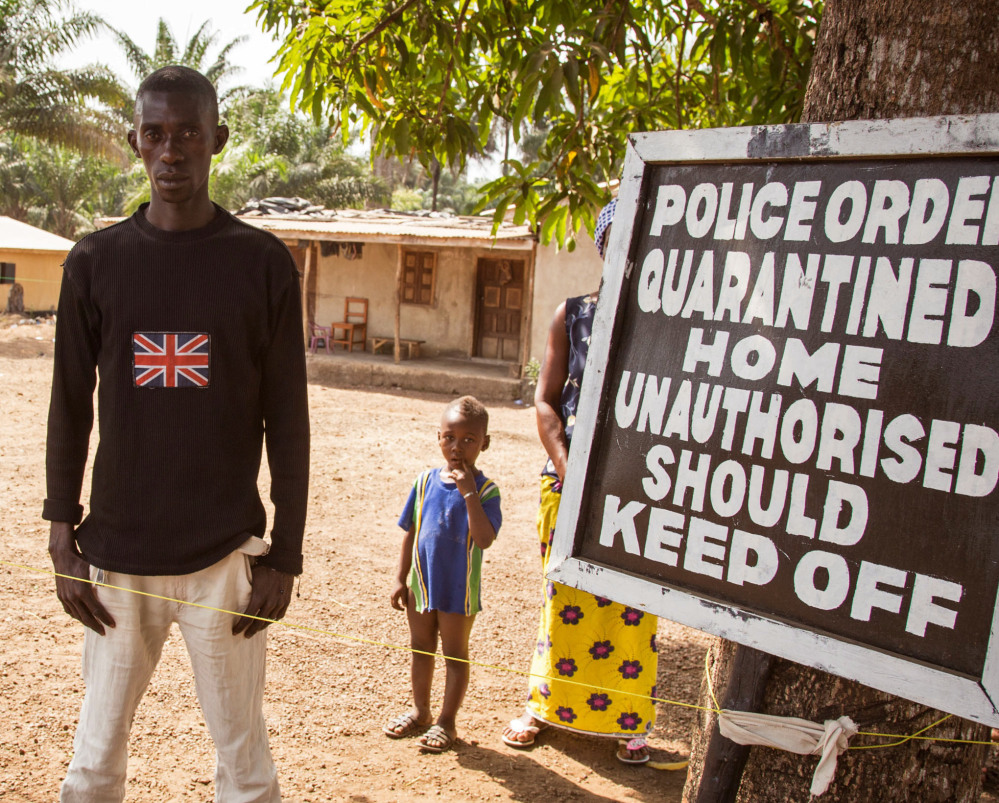 A man in Kambia, Sierra Leone, outside his home next to a board stating that his home is under quarantine due to the Ebola virus.
