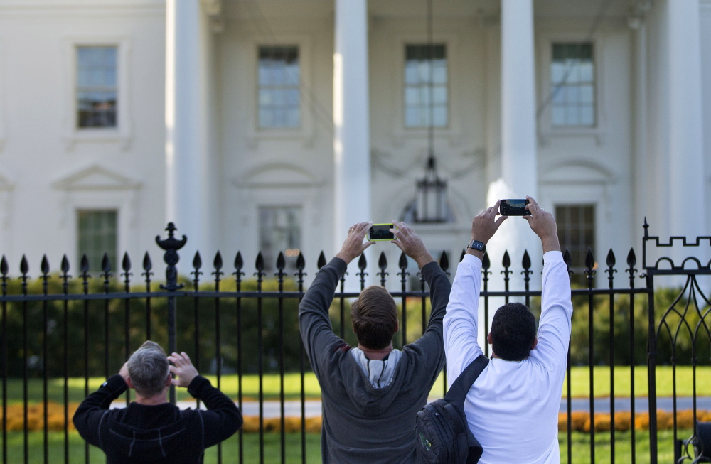 Visitors take photos from the sidewalk in front of the White House. The Secret Service is adding more spikes to the White House fence.