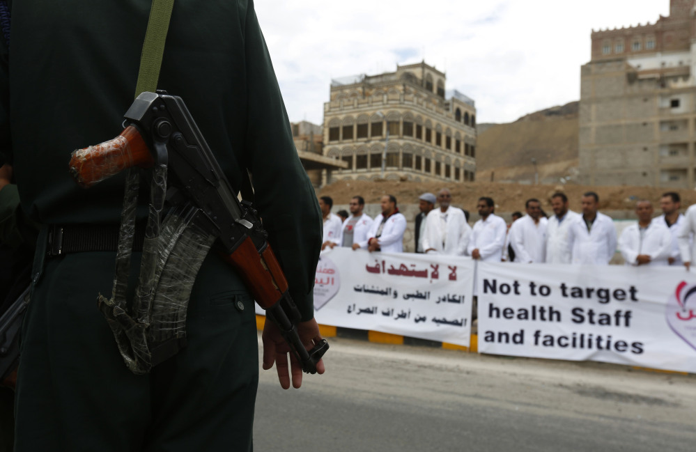 A soldier stands guard as Yemeni health workers attend a rally demanding the lifting of the blockade on Yemen, in front of the U.N. building in Sanaa, Yemen, on Thursday.