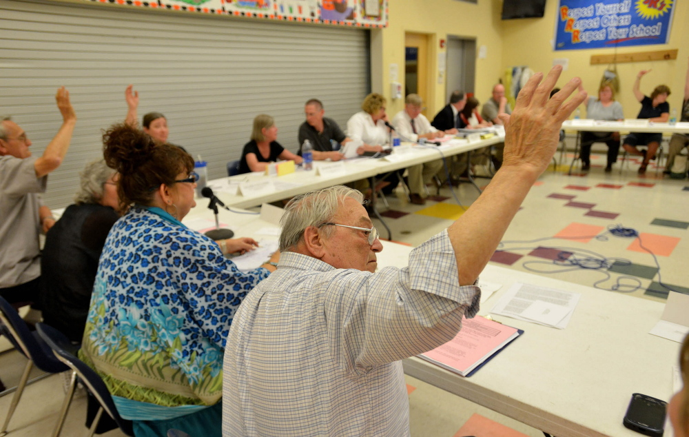 """Allan Laney, a member of the School Administrative District 54 board, votes to keep the Skowhegan Area High School team name """"Indians"""" during a board meeting Thursday at Skowhegan Junior High School. A proposed name change was voted down."""