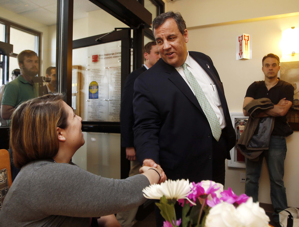 Stephanie Rhodes, left, shakes hands with New Jersey Gov. Chris Christie as he arrives for a roundtable discussion Thursday at the Farnum Center in Manchester, N.H.