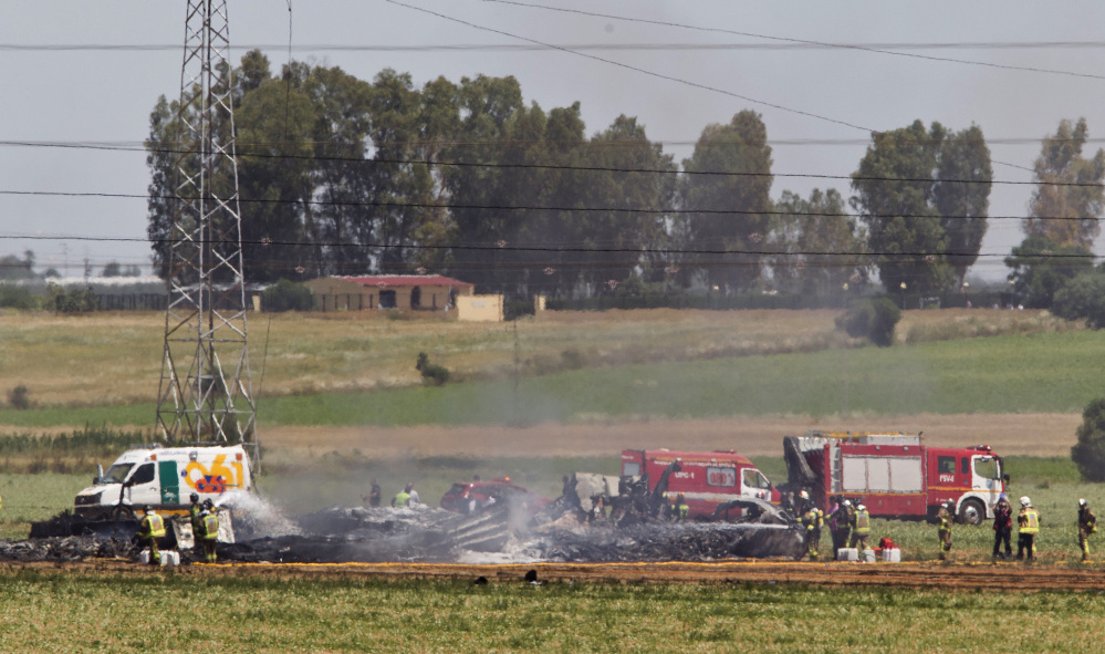 Emergency services personnel work in the area after a plane crash near the Seville airport, in Spain, on Saturday. A military transport plane crashed near southwestern Seville airport, killing four crew members.
