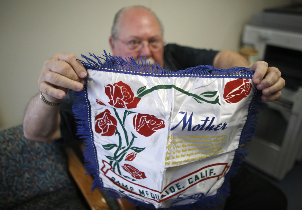 Donald Lamoureux displays a pillow sham, which his son bought on eBay, at a senior center May 5 in Millville, Mass. Dominic O'Gara, an artilleryman who served in Italy during World War II, had mailed the sham from an Army base in California to his mother in Millville in 1942.