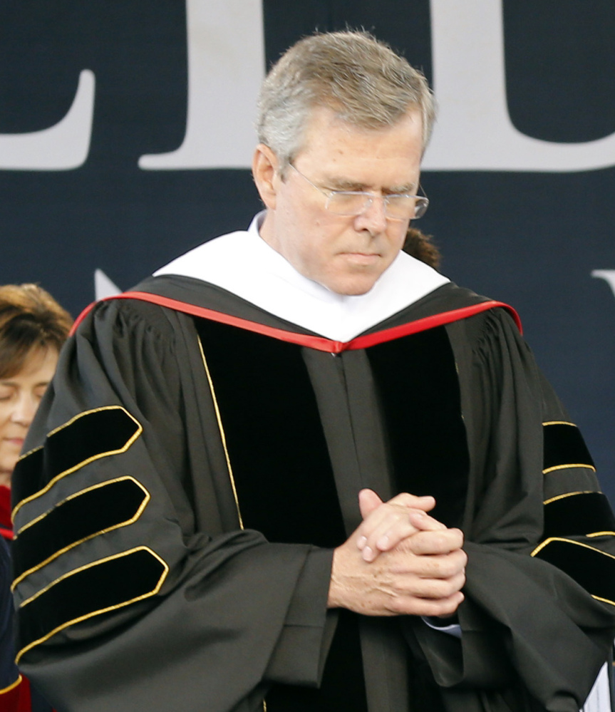 Jeb Bush bows his head in prayer during  commencement at Liberty University on Saturday.
