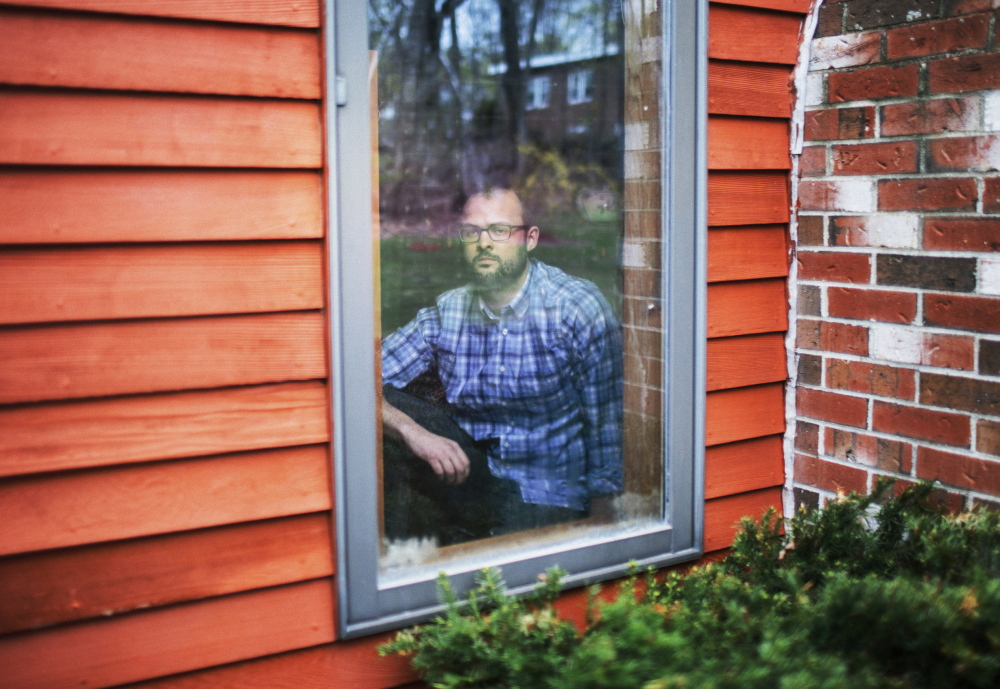 Matt Lauzon looks out from his childhood home in Biddeford. When he was a teen, he says, Biddeford police officer Stephen Dodd would park nearby and flash his lights to intimidate him and to remind him he was being watched.
