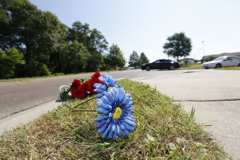 A bouquet of Mother's Day roses and two silk flowers are placed along the sidewalk on Sunday near the site where two Hattiesburg, Miss., police officers were fatally shot during a traffic stop the night before, in Hattiesburg.