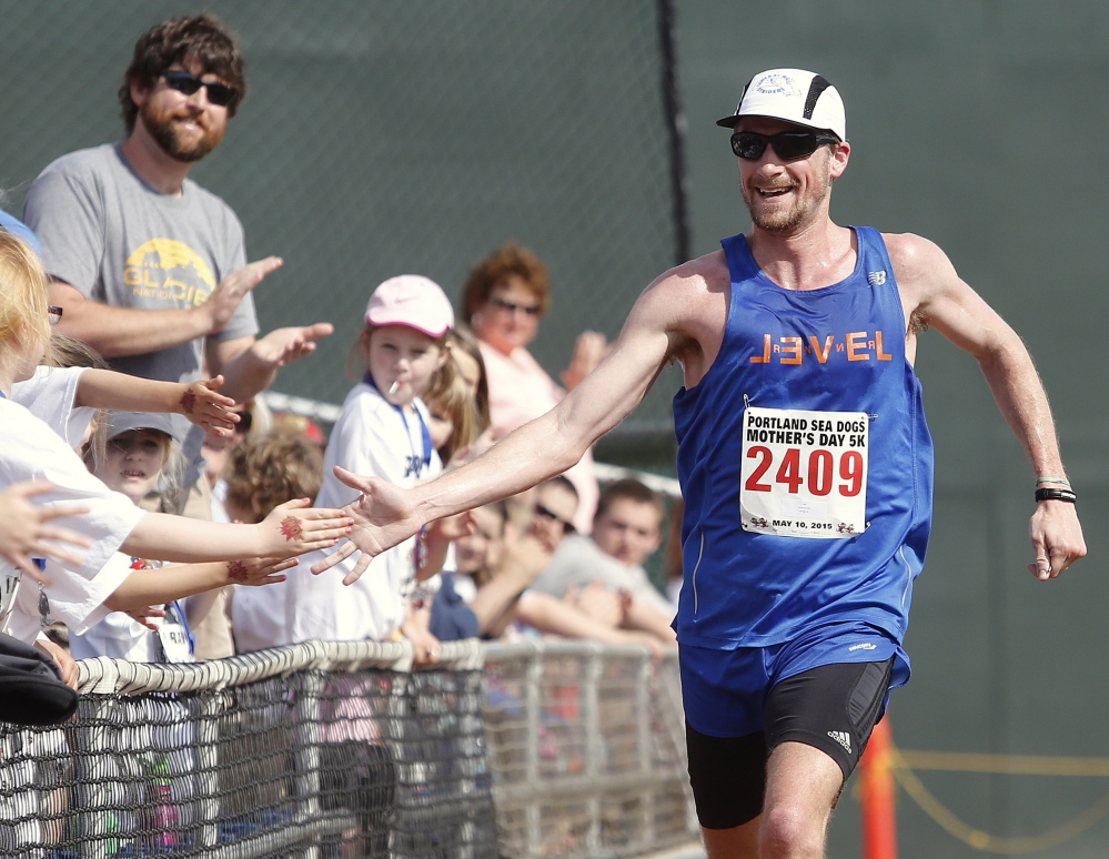 Derek Davis/Staff Photographer Dan Vassallo, 30, of Peabody, Mass., greets fans as he finishes first overall in Sunday's Portland Sea Dogs Mother's Day 5K. The race ended at Hadlock Field.