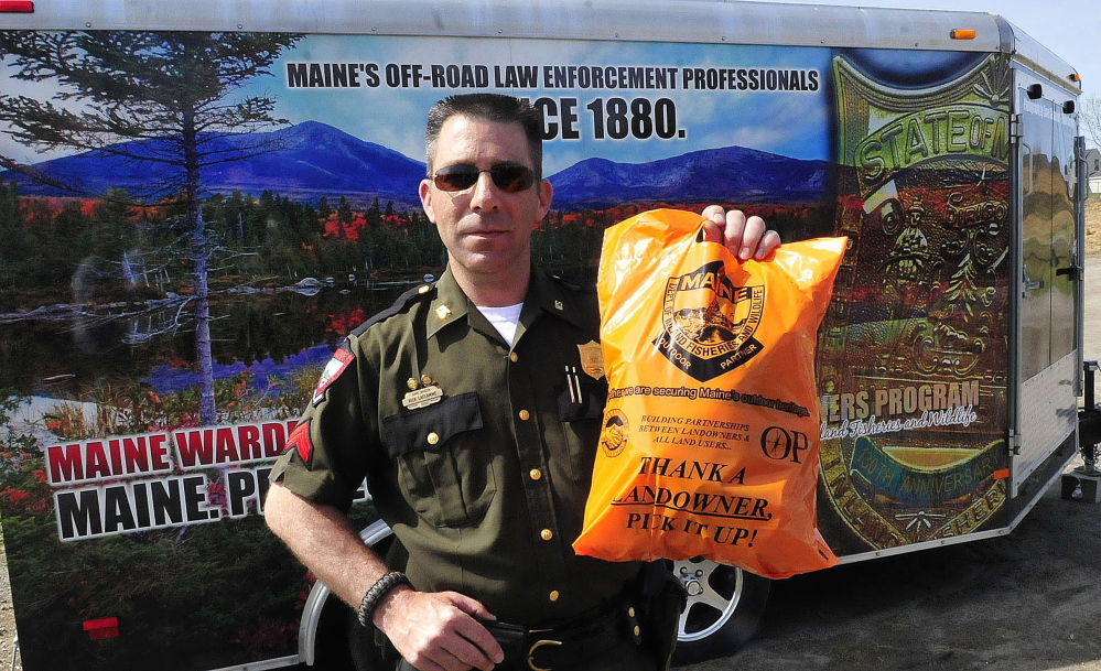 Game Warden Rick LaFlamme holds one of the trash bags that will be distributed around the state in a program to improve relations between landowners and land users. Visitors would remove their own trash and any left by others.