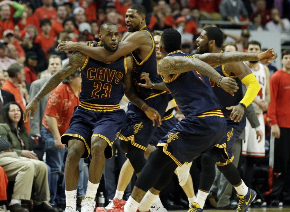 LeBron James, left, is mobbed by his teammates after his buzzer-beating jumper gave the Cleveland Cavaliers an 86-84 win Sunday over the Chicago Bulls, evening the best-of-seven series at two games apiece.