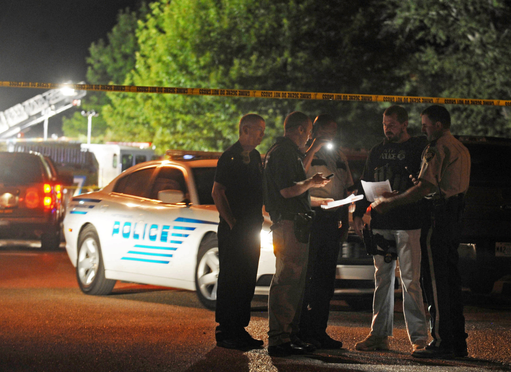 Police study information on suspects wanted in the fatal shooting of two Hattiesburg, Miss., police officers, Saturday night.